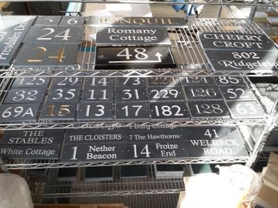 slate house signs on a rack ready for dispatch
